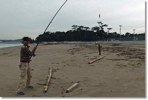 砂浜でアイナメを釣り上げた人