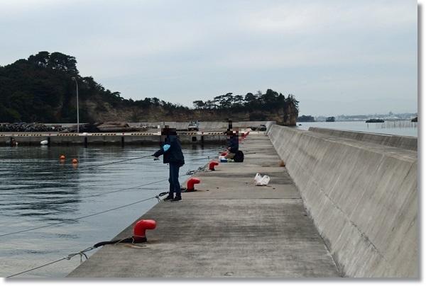 桂島の堤防で釣りをする人々