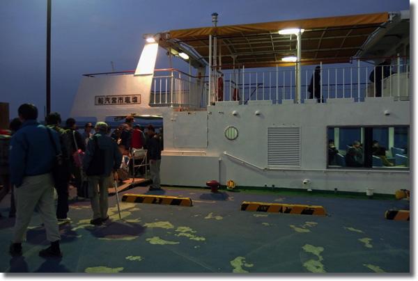 桂島の桟橋からフェリーに乗り込む人々