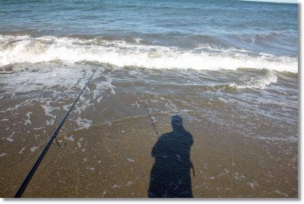 波打ち際に映る釣り人の影