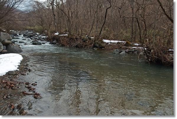 岸辺に雪が残った渓流