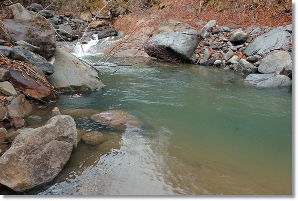 水が濁り気味の渓流