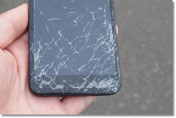 手に持った液晶画面が粉々に割れたスマートフォン