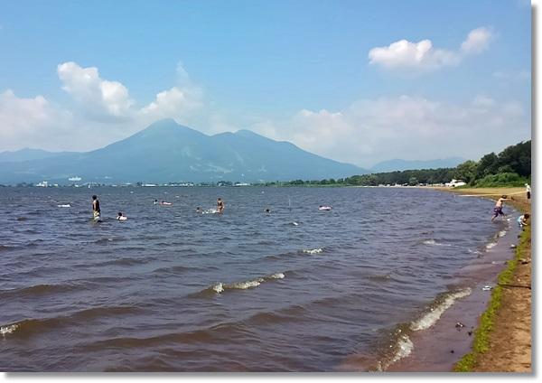 磐梯山がの見える猪苗代湖で水遊びをする人々