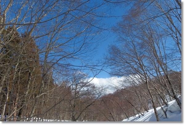 雪が残る初春の山に広がる青空