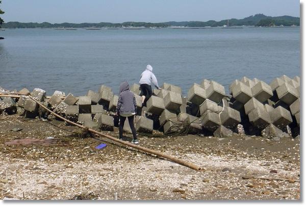海辺のテトラを乗り越える女性