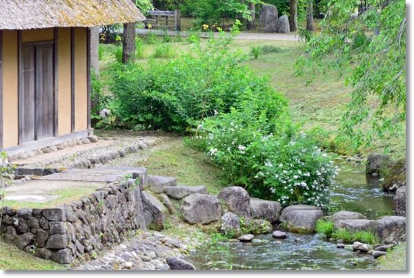 茅葺き家屋と小川